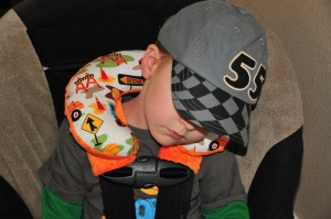 Little boy sleeping comfortably in car seat with head resting on Lou Bugs Boutique Travel Neck Pillow