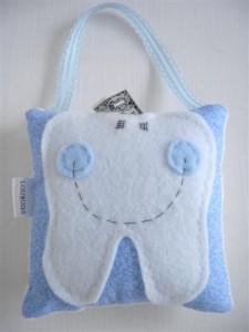 Lou Bugs Boutique hanging pastel blue and white happy faced tooth pillow