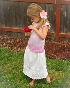 little girl with white crochet trim skirt looking at rose