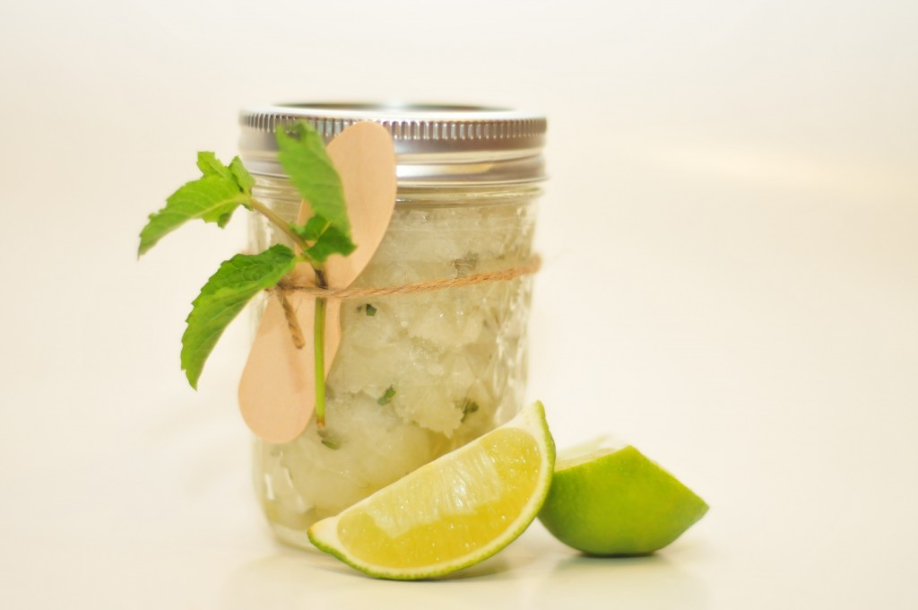 Jar of sugar scrub w/ a mint leaf and wooden spoon tied with twine around it. limes set in front.