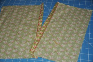 two pieces of green flowered fabric with opposite sides finished with a zigzag seam