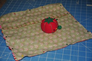tomato pin cushion sitting on top of fabric