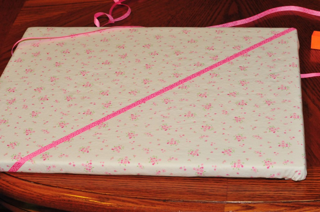ribbon laying at a right angle across fabric covered canvas.
