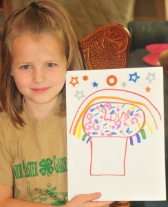 little girl holding up a big white card with a cupcake drawn on the front