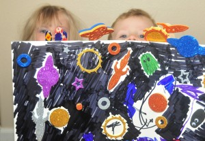 two little heads peaking from behind an outer space scene on a piece of foam board.
