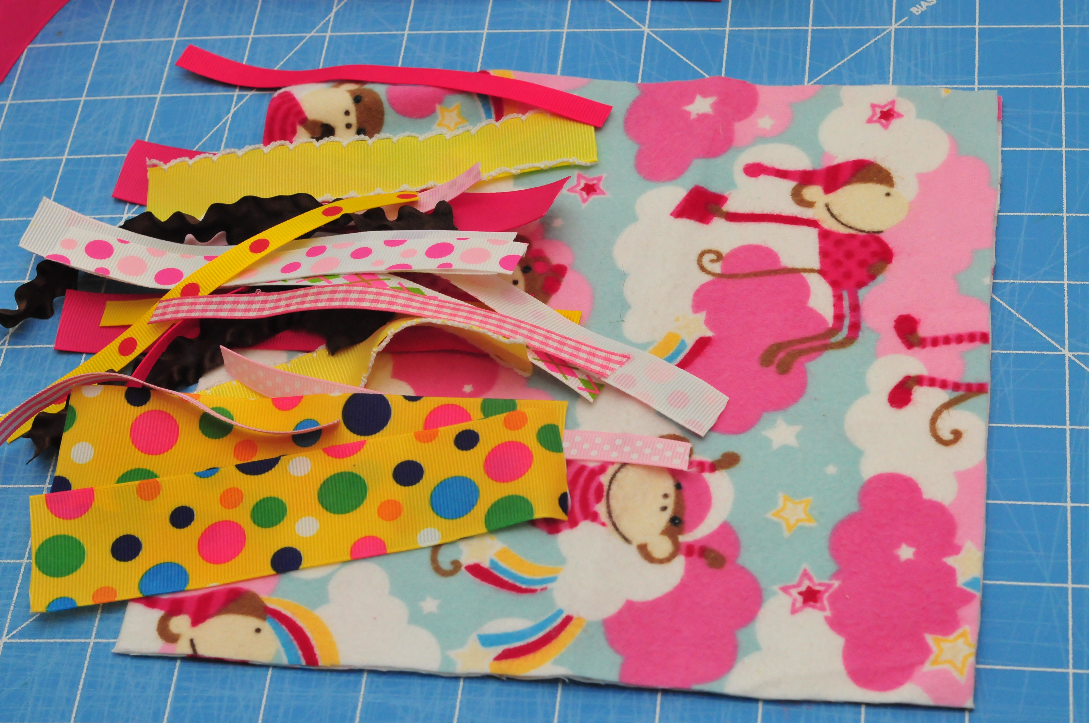 pink and blue monkeys in pjs on fabric with scraps of ribbon on top.