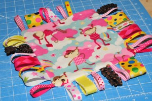 taggie blanket with one section of ribbon missing.