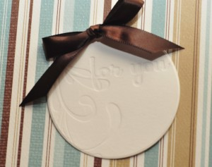 gift tag w/ debossed image and brown ribbon