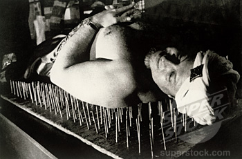 Mid adult man lying on a bed of nails