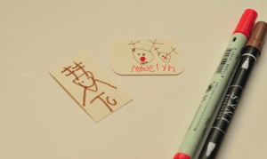 pens and little rectangle paper with kid drawings