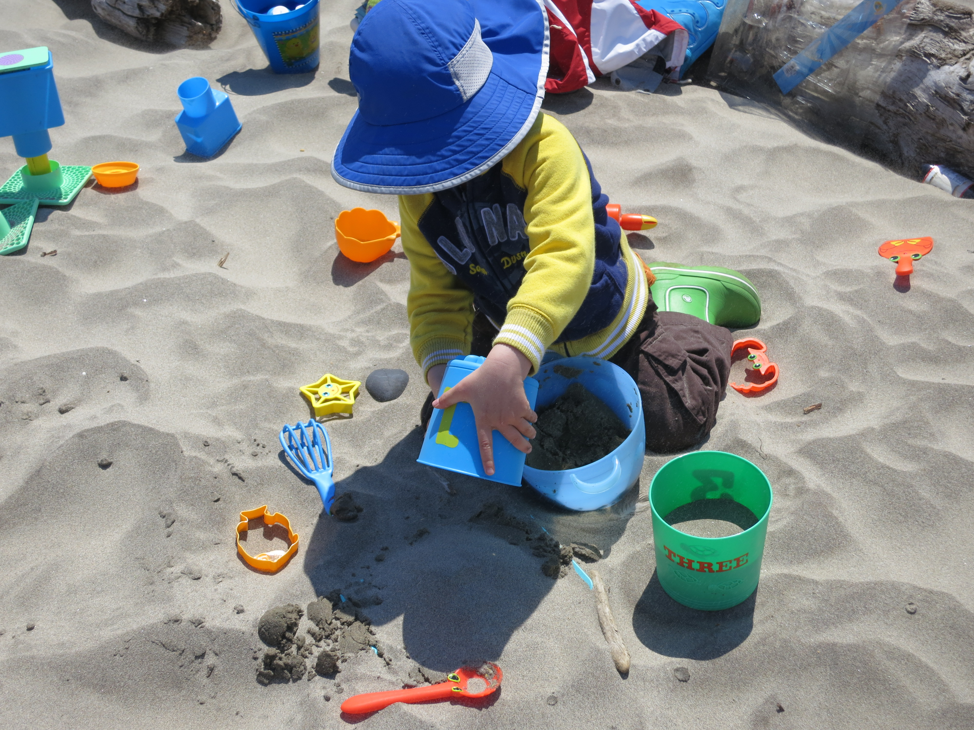 little boy playing with sand toys